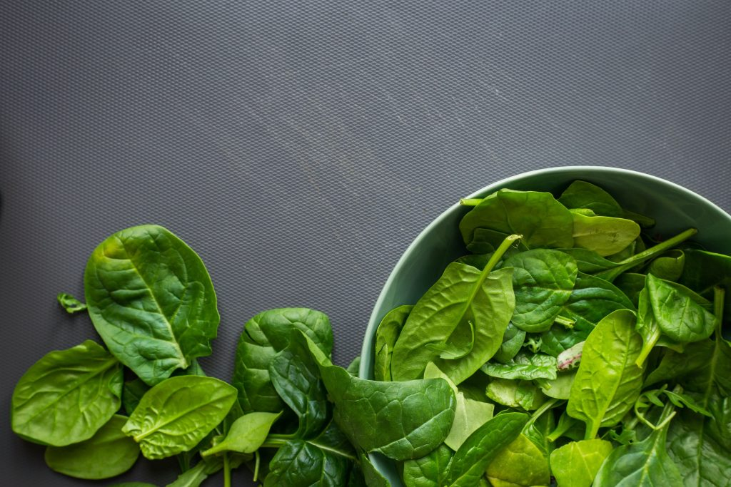 Some raw spinach leaves against a grey background, some in a metal bowl.