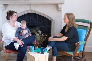 two women sitting together talking one is holding her baby