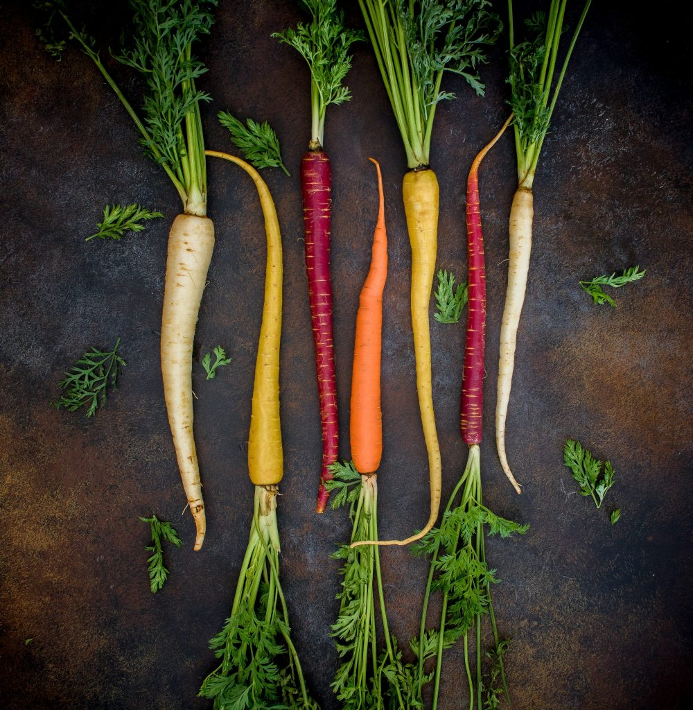 thin coloured carrots on a dark background