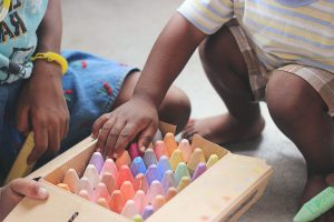 children's hands looking at a box of crayons. Two children with brown skin looking into a box of pastel coloured chalks.